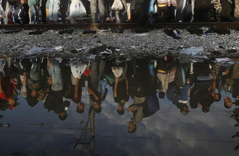 Syrian refugees are reflected in a puddle as they wait for their turn to enter Macedonia at Greece's border (photo credit: REUTERS)
