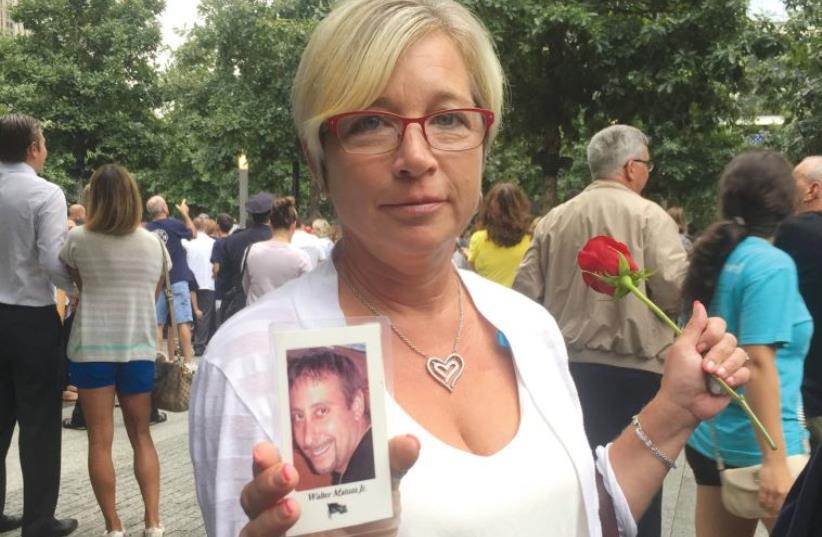 DENISE MATUZA holds her husband's picture at the memorial on Friday. He died in the North tower 14 years ago (photo credit: DANIELLE ZIRI)