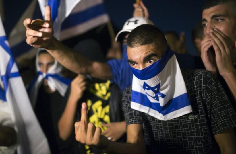 A right-wing Israeli activist gestures during a counter-protest against supporters of hunger-striking Palestinian detainee Mohammed Allan (photo credit: REUTERS)