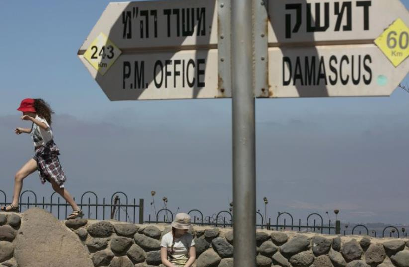 Girls play near a sign at Mount Bental, an observation post on the Israeli side of the Golan Heights, overlooking the Syrian side of the Kuneitra crossing (photo credit: REUTERS/BAZ RATNER)