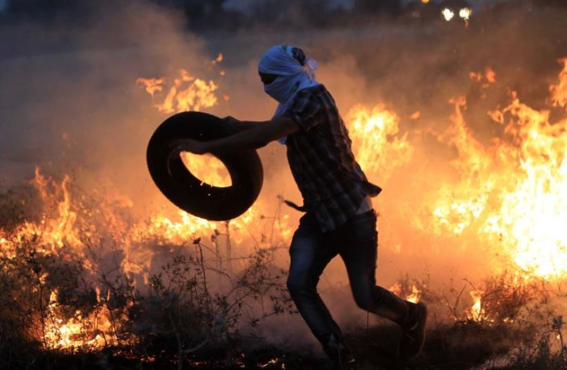 A Palestinian protester throws a tire into a fire during clashes with Israeli security forces (photo credit: AFP PHOTO)