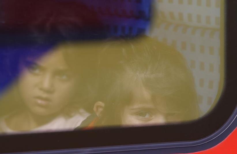 Migrant girls look through a regional train window at the Munich railway station