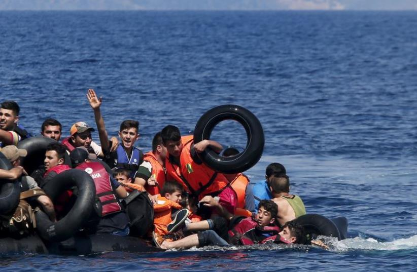 Syrian and Afghan refugees struggle to stay afloat after their dinghy collapses just off the coast of Greece (photo credit: REUTERS)