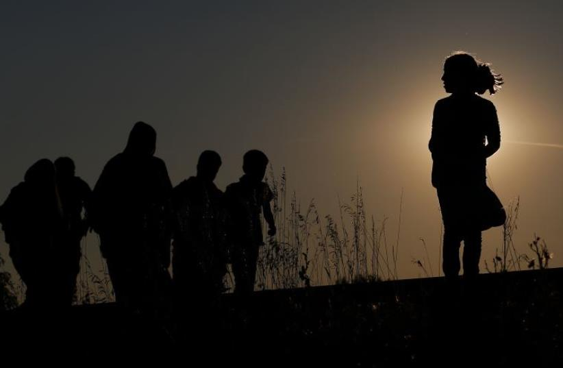 Migrants walk along rail tracks on sunset close to a migrant collection point in Roszke, Hungary (photo credit: REUTERS)