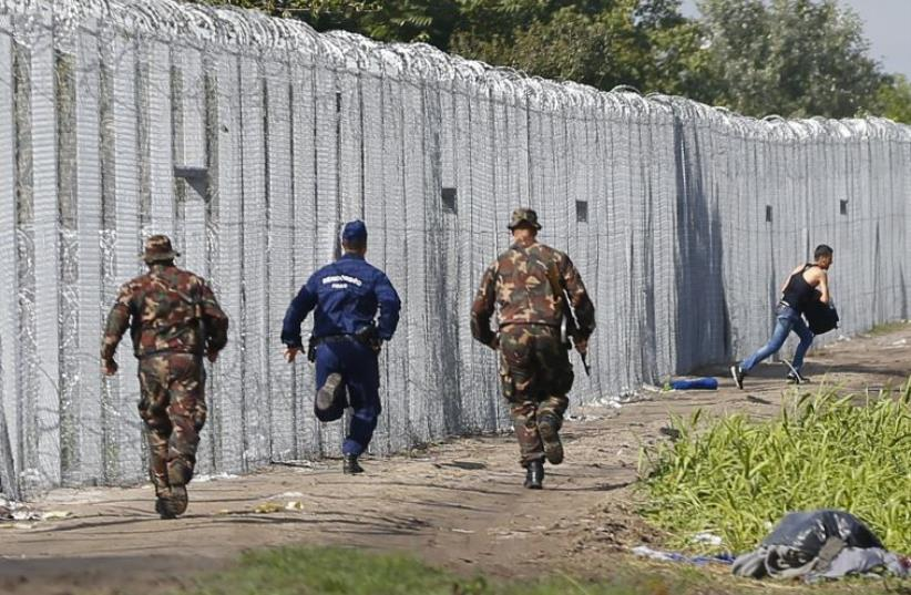A migrant crosses the boarder fence as soldiers and police try to catch him