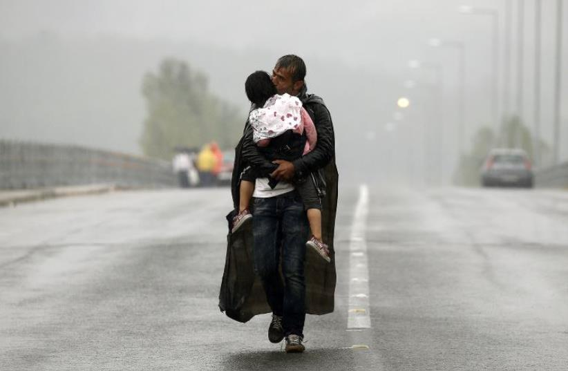 A Syrian refugee kisses his daughter as he walks through a rainstorm towards Greece's border with Macedonia, near the Greek village of Idomeni (photo credit: REUTERS)