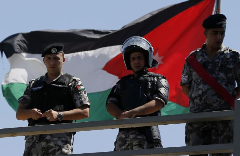Jordanian riot police stand guard in front of a Jordanian flag as protesters hold a demonstration against Israel in Amman (photo credit: REUTERS)