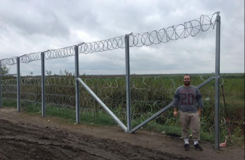THE WRITER poses next to the fence along the Hungarian border (photo credit: Courtesy)