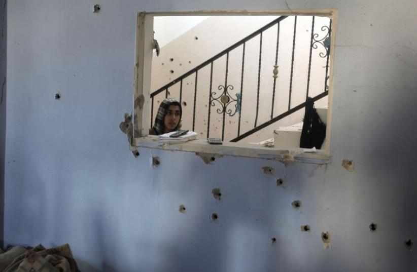 Bullet impacts are seen on a wall as a Palestinian man inspects a house where two members of the military wing of Hamas, the Ezzedine al-Qassam Brigades, and a civilian were killed on March 22, 2014 during an Israeli military operation in the northern West Bank of Jenin.  (photo credit: JAAFAR ASHTIYEH / AFP)