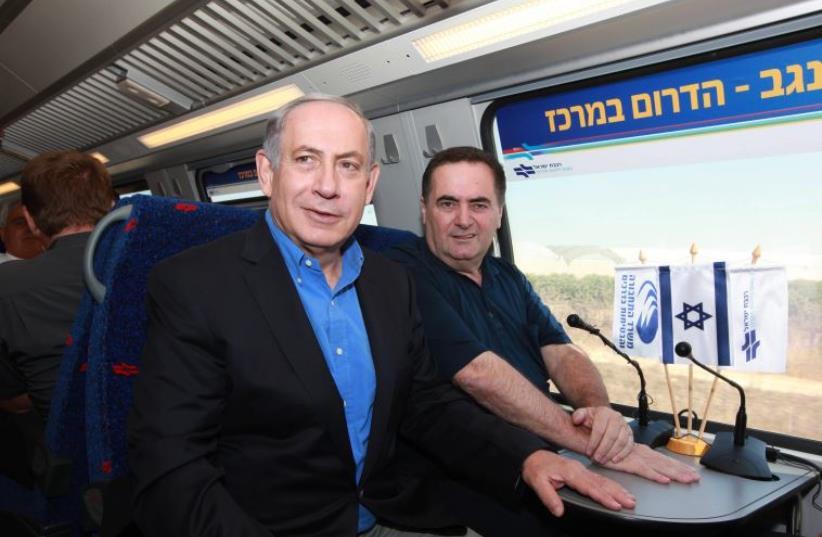 Prime Minister Benjamin Netanyahu and Transportation Minister Yisrael Katz ride an Israel Railways train (photo credit: ELIYAHU HERSHKOVITZ/POOL)