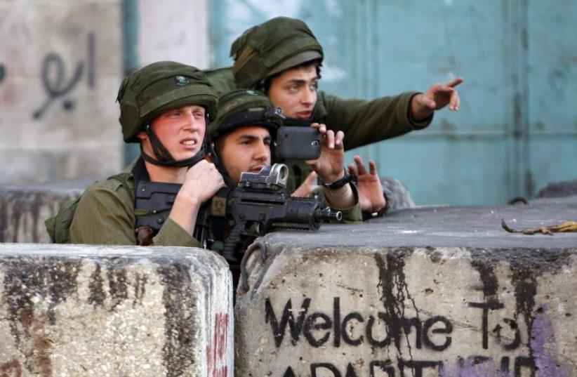 An Israeli soldier uses his mobile to take pictures during clashes with Palestinian stone-throwers in the West Bank city of Hebron March 6, 2015 (photo credit: MUSSA QAWASMA / REUTERS)