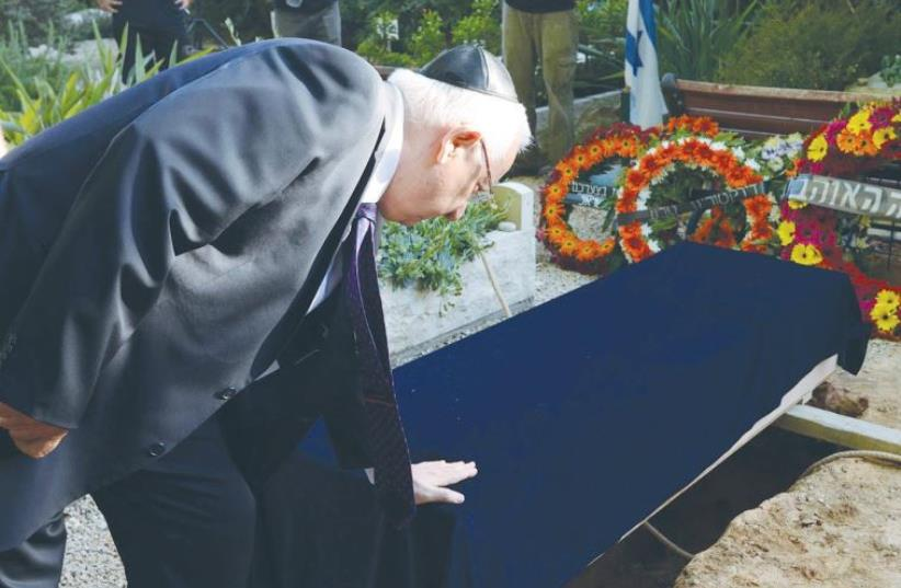 PRESIDENT REUVEN RIVLIN pays his respects at the funeral of former Supreme Court justice Mishael Cheshin at Kibutz Givat Hashlosha (photo credit: MARK NEYMAN / GPO)