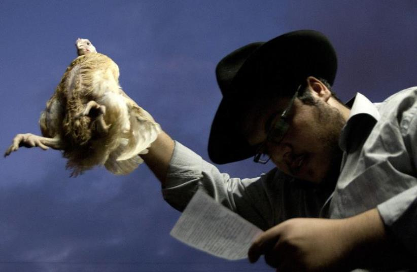 An Ultra-Orthodox man holds a chicken as he performs the Kapparot ritual ahead of Yom Kippur [Illustrative] (photo credit: REUTERS)