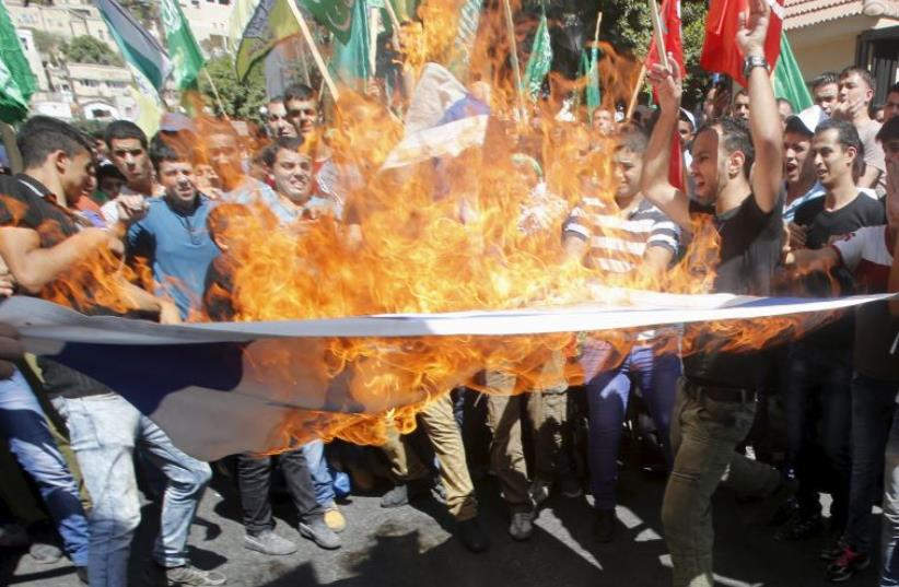 Palestinian protesters burn an Israeli flag during a protest against the Israeli police raid on Jerusalem's al Aksa mosque (photo credit: REUTERS)