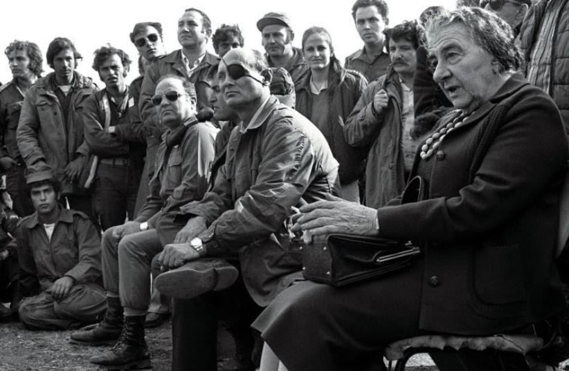 Then-prime minister Golda Meir (R) and her defense minister, Moshe Dayan, meet with Israeli soldiers at a base on the Golan Heights after intense fighting during the 1973 Yom Kippur War (photo credit: REUTERS)