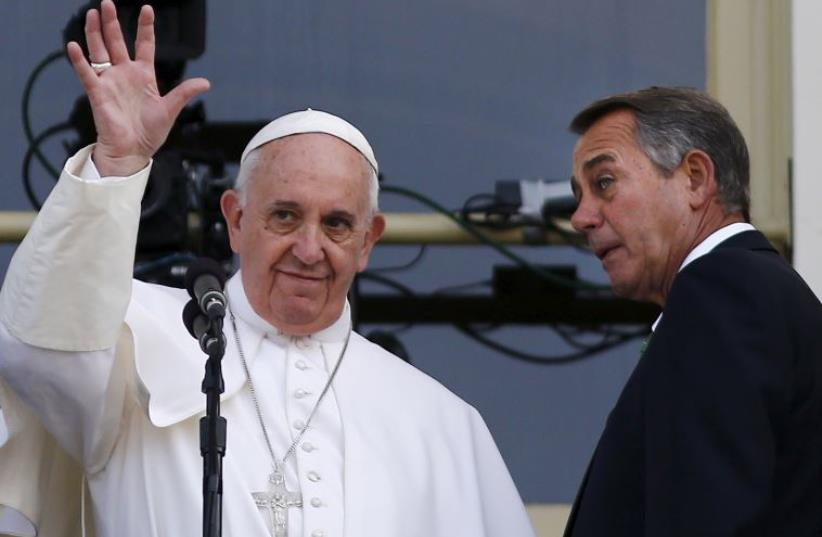 Pope Francis waves from the Speaker's Balcony after concluding his addresses, before a joint meeting with the US Congress, as Speaker of the House John Boehner (R) looks at him on Capitol Hill in Washington  (photo credit: REUTERS)