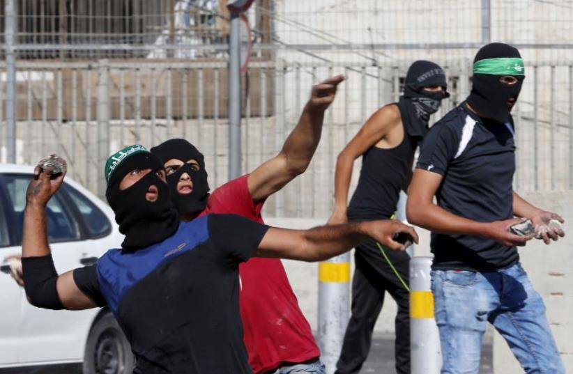 Palestinians hurl stones towards Israeli Border Police during clashes at a checkpoint between Shuafat and Jerusalem September 18, 2015 (photo credit: REUTERS)