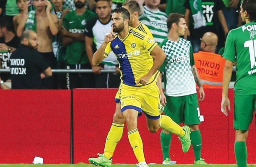 Maccabi Tel Aviv striker Eden Ben-Basat (center) celebrates after breaking the deadlock in last night's 2-0 win over Maccabi Haifa at Haifa Stadium (photo credit: ERAN LUF)