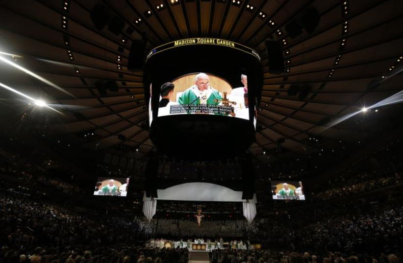 Pope Francis is shown on several large screens as he celebrates mass at Madison Square Garden in New York (photo credit: REUTERS)