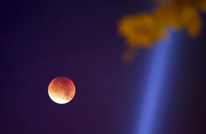 The Moon, appearing in a dim red color, is covered by the Earth's shadow during a total lunar eclipse over Paris (photo credit: REUTERS)