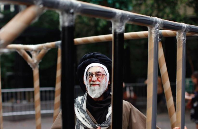 A PROTESTER wearing a mask depicting Iran's Supreme Leader Ayatollah Ali Khamenei stands in a fake jail during protests outside the UN headquarters in New York in 2011. Iran's human rights abuses seem to be off the agenda this year. (photo credit: REUTERS)