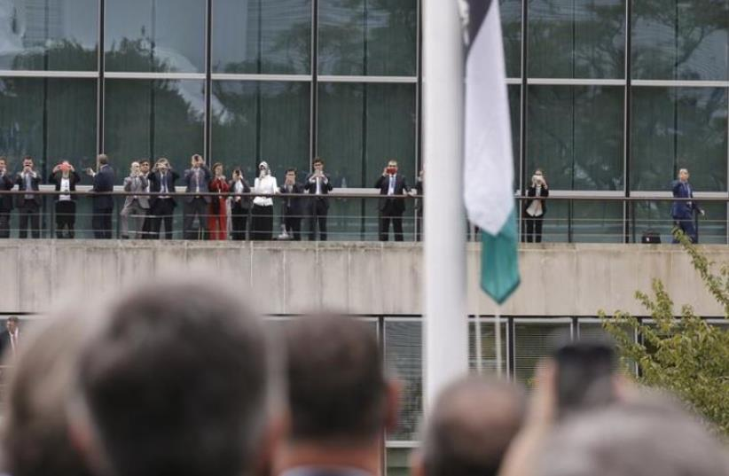 Onlookers take photographs as the Palestinian flag is being raised by Palestinian President Mahmoud Abbas (not pictured) in a ceremony outside the United Nations during the 70th session of the U. N. General Assembly in New York, September 30, 2015. Even though Palestine is not a member of the United (photo credit: REUTERS)