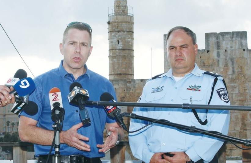 PUBLIC SECURITY MINISTER Gilad Erdan speaks to reporters yesterday outside Jerusalem's Old City. To his right is Acting Police Commissioner Asst.-Ch. Bentzi Sau (photo credit: MARC ISRAEL SELLEM)