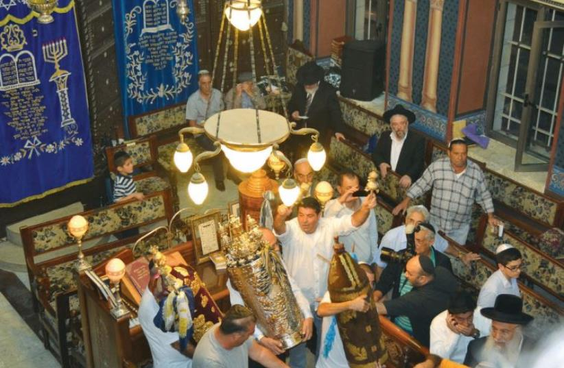 Men dance with Torah scrolls at the Ades Synagogue in Jerusalem (photo credit: JPOST STAFF)