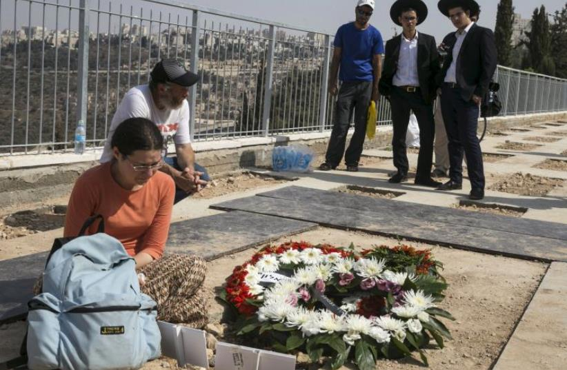 Mourners stand beside the fresh grave of Eitam and Na'ama Henkin after their funeral at a Jerusalem cemetery (photo credit: REUTERS)