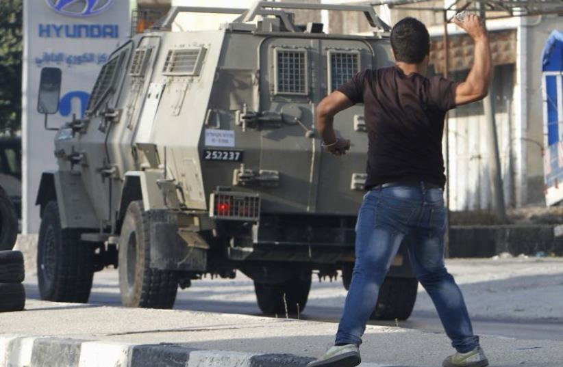 A Palestinian youth hurls stones at Israeli troops during clashes following an Israeli army raid in Nablus (photo credit: REUTERS)