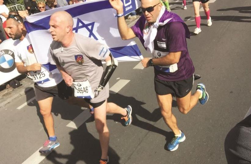 AFTER BEING severely injured while leading a patrol along the Gaza border in 2012, and currently on rehabilitative leave from the IDF Givati Brigade, Capt. Ziv Shilon (center) kept a promise he made to friends, family and himself by meeting his goal of running the Berlin Marathon on September 27. (photo credit: Courtesy)