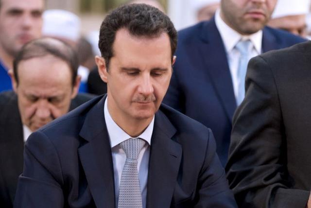 Syria's President Bashar Assad attends prayers on the first day of Eid al-Adha at al-Adel mosque in Damascus (photo credit: REUTERS)