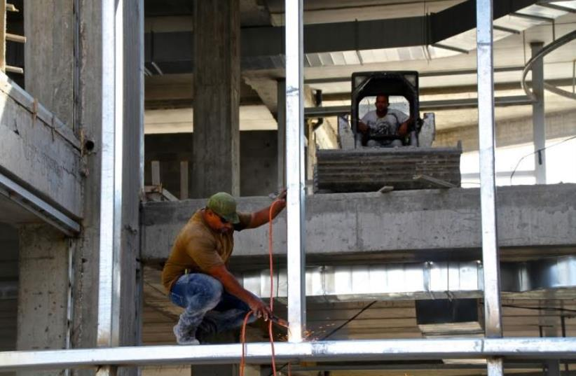 Construction workers build new mall at the Gush Etzion junction in the West Bank (photo credit: TOVAH LAZAROFF)