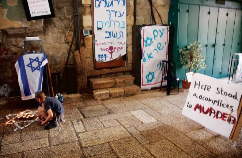 A child pays homage at the site in Jerusalem's Old City where Rabbi Nehemia Lavi and Aharon Banita were stabbed to death on October 3 (photo credit: MARC ISRAEL SELLEM/THE JERUSALEM POST)