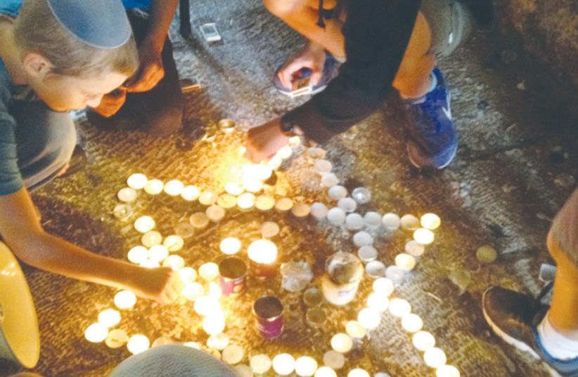 BOYS LIGHT memorial candles at the scene of two terrorist attacks (photo credit: DANIEL K. EISENBUD)