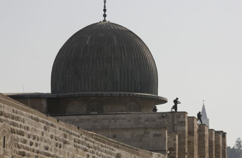Israeli police officers take positions on the roof of the al-Aksa mosque during clashes with Palestinians in Jerusalem's Old City (photo credit: REUTERS)