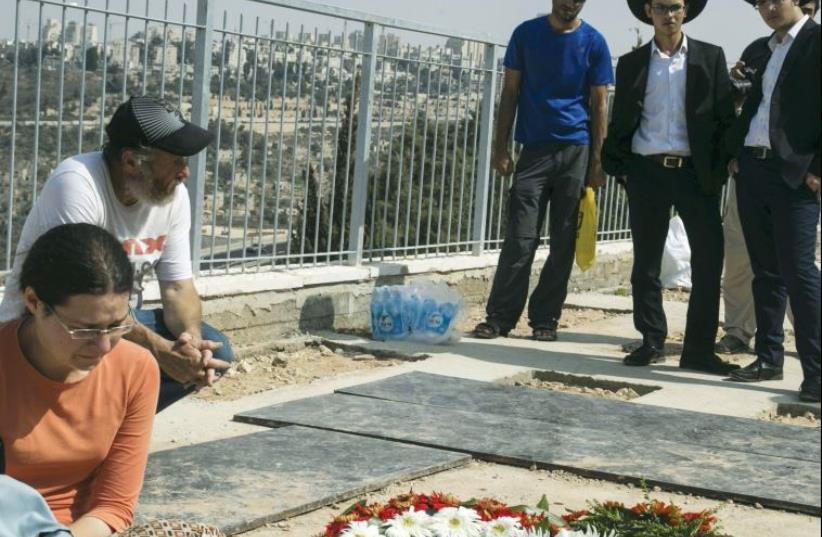 Mourners stand beside the fresh grave of Eitam and Na'ama Henkin (inset) after their funeral in Jerusalem on October 2 (photo credit: REUTERS/BAZ RATNER)