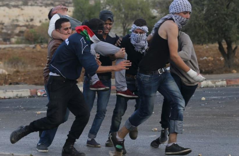 A wounded Palestinian is carried off during clashes with IDF troops near Ramallah (photo credit: REUTERS)