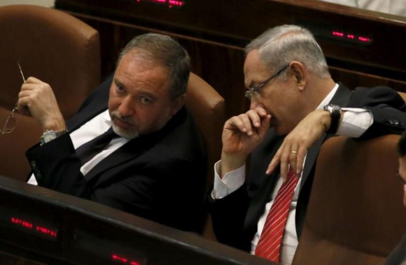 Prime Minister Benjamin Netanyahu (R) confers with Yisrael Beytenu chief Avigdor Liberman in the Knesset (photo credit: AFP PHOTO)