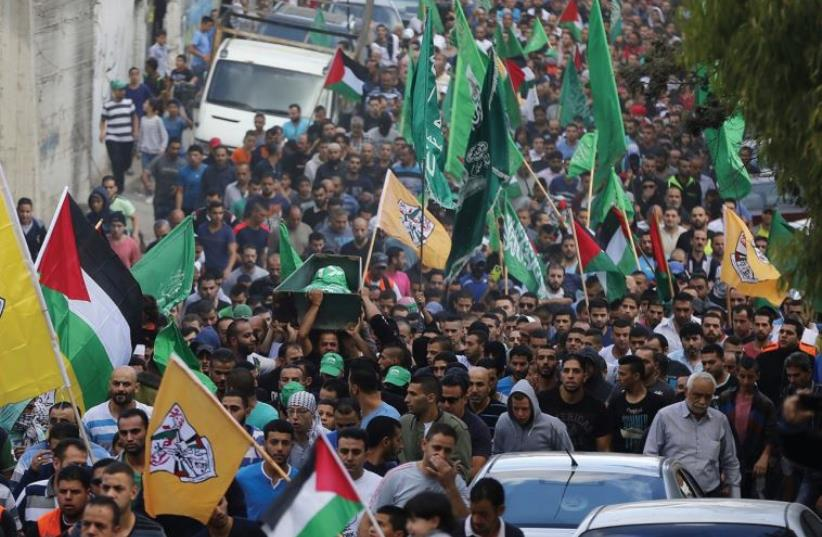 MOURNERS CARRY the body of a Palestinian killed in clashes with Israeli forces in east Jerusalem. (photo credit: REUTERS)