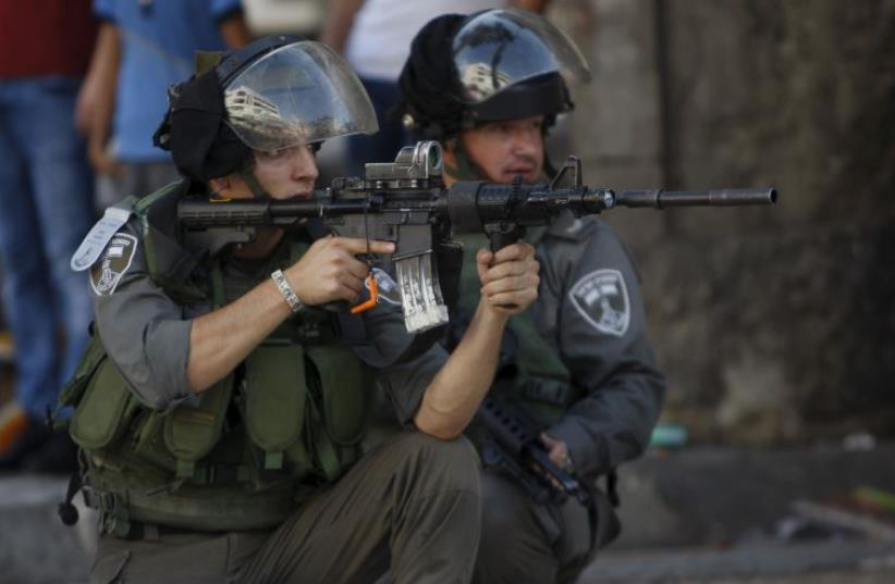 An Israeli border policeman aims his weapon at Palestinians during clashes in Hebron (photo credit: REUTERS)