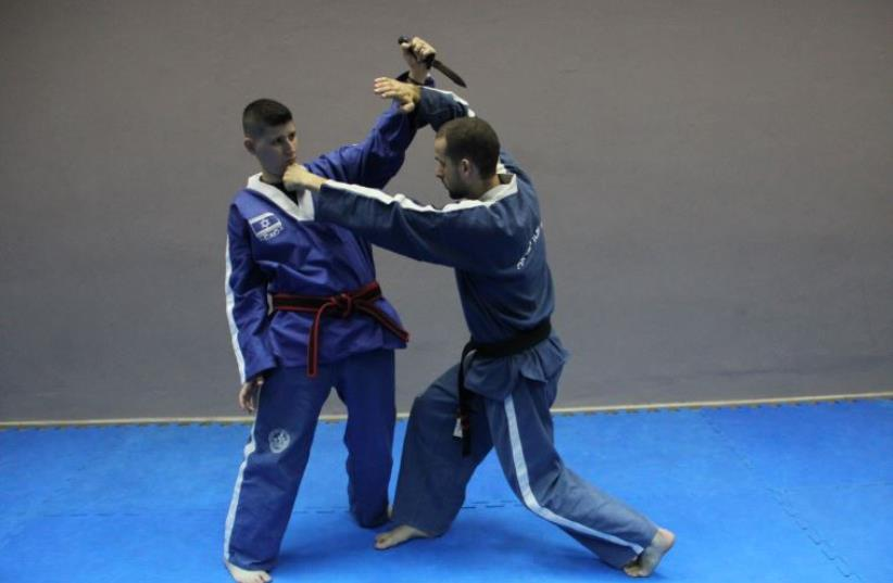 Senior Israeli Krav Magen instructor Yonatan Graber (right) and his trainer, Maor Hakak, displaying a defense against a forward knife attack (photo credit: Courtesy)