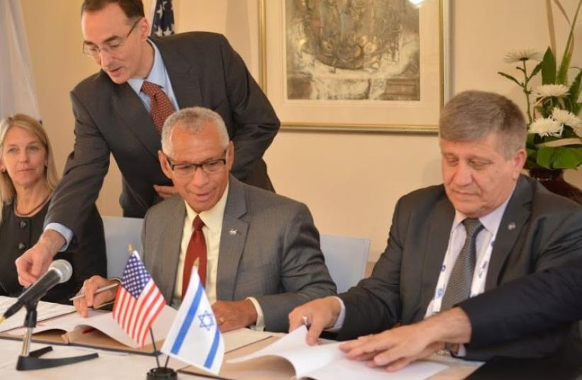 NASA Administrator Charles Bolden (left) and Israel Space Agency director Menachem Kidron sign a cooperation agreement in Jerusalem (photo credit: ISRAEL BEN-ELI)