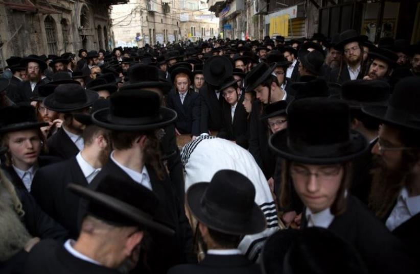 Thousands of Ultra-Othodox Jews walk behind the body of Rabbi Yishayahu Krishevsky during his funeral in Jerusalem (photo credit: AFP PHOTO)