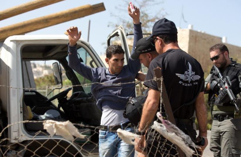 Border police check a Palestinian driver on a road outside the Palestinian neighbourhood of Jabel Mukabaer in East Jerusalem (photo credit: MENAHEM KAHANA / AFP)
