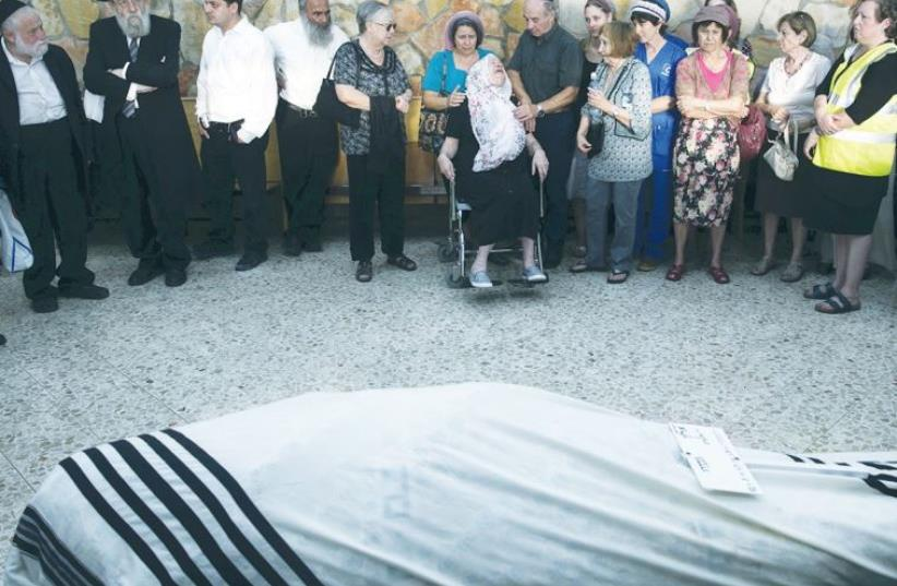 JERUSALEM BUS attack victim Alon Govberg's wheelchair ridden mother mourns the 51-year-old at his funeral yesterday, attended by hundreds (photo credit: REUTERS/BAZ RATNER)