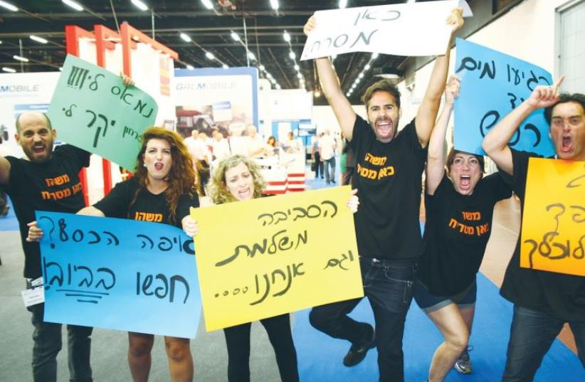 ACTIVISTS AT the WATEC exhibition at the Tel Aviv Convention Center yesterday call for implementing Israeli water tech at home (photo credit: MAPAL GREEN ENERGY)
