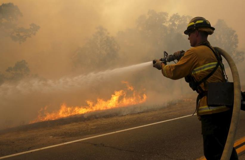 A firefighter uses a hose to extinguish flames. (photo credit: REUTERS)