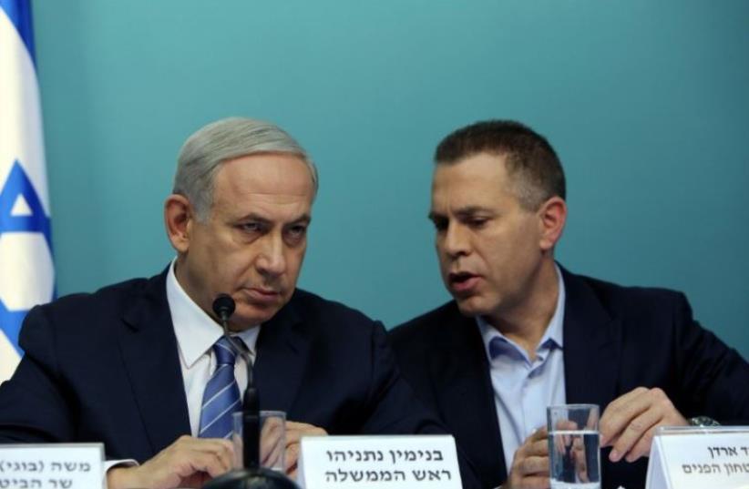 Prime Minister Benjamin Netanyahu listens to Public Security Minister Gilad Erdan (R) during a press conference in Jerusalem (photo credit: AFP PHOTO)