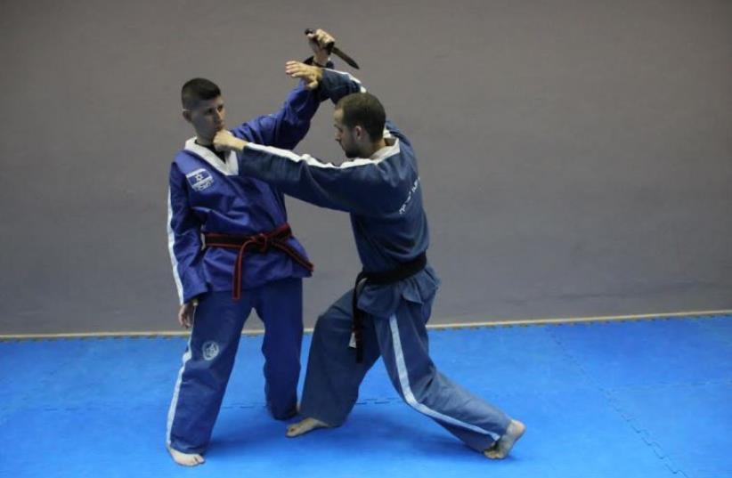 Senior Israeli Krav Magen instructor Yonatan Graber (right) and his trainer, Maor Hakak, displaying a defense against a forward knife attack.  (photo credit: Courtesy)